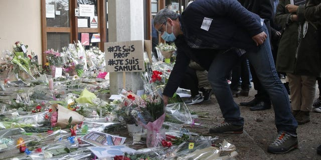 "A man lays a flower outside the school where a slain history teacher was working, Saturday, Oct. 17, 2020, in Conflans-Sainte-Honorine, northwest of Paris. French President Emmanuel Macron denounced what he called an ""Islamist terrorist attack"" against a history teacher decapitated in a Paris suburb Friday, urging the nation to stand united against extremism. The teacher had discussed caricatures of Islam's Prophet Muhammad with his class, authorities said. The suspected attacker was shot to death by police after Friday's beheading. (AP Photo/Michel Euler)"
