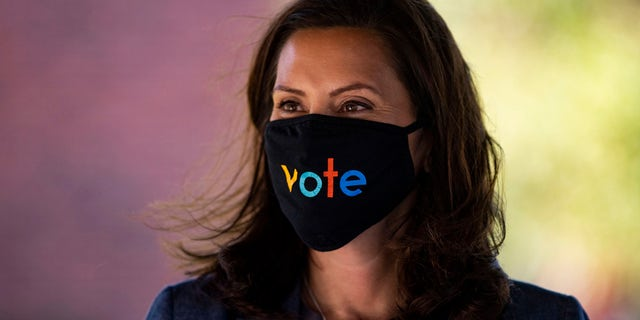 "Michigan Gov. Gretchen Whitmer wears a mask with the word ""stem"" displayed on the front during a roundtable discussion on healthcare, Wednesday Oct. 7, 2020, in Kalamazoo, Ek. (Nicole Hester/Ann Arbor News via AP)/"