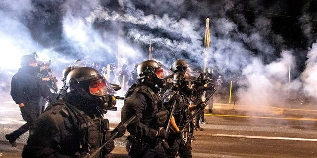 Police use chemical irritants and crowd control munitions to disperse protesters during the 100th consecutive day of demonstrations in Portland, Ore., on Saturday, Sept. 5, 2020. According to an officer, police responded with stronger tactics after a molotov cocktail was thrown.(AP Photo/Noah Berger)