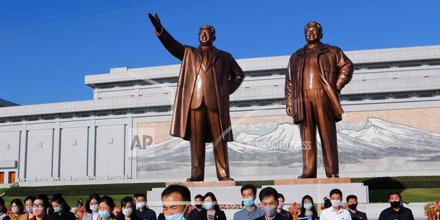 People visit the Mansu Hill to lay flowers to the bronze statues of former North Korean leaders Kim Il Sung and Kim Jong Il in Pyongyang, North Korea, Saturday, Oct. 10, 2020, on the occasion of the 75th founding anniversary of the country's Workers' Party. (AP Photo/Cha Song Ho)