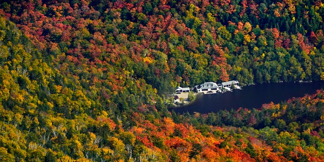 Waterfront buildings at The Ausable Club are surrounded by a forest of changing colors as viewed from Gothics Mountain, Saturday, Sept. 26, 2020, in New York's Adirondack Park.