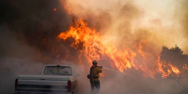 Firefighter Raymond Vasquez battles the Silverado Fire Monday, 十月. 26, 2020, in Irvine, 牛犊.