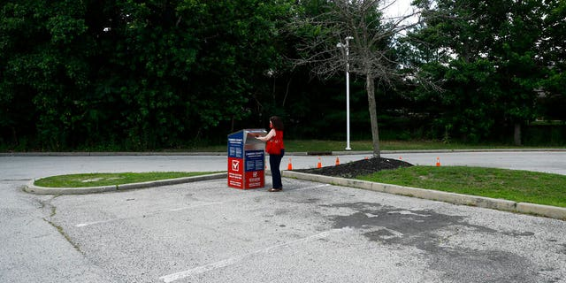 FILE - In this July 1, 2020, file photo, a New Jersey woman drops off her ballot for the New Jersey primary election at a vote-by-mail drop box in a parking lot at Camden County College in Cherry Hill, N.J. Amid the global pandemic, more people than ever are expected to bypass their polling place and cast absentee ballots for the first time. Voters marking ballots from home could lead to an increase in the kinds of mistakes that typically would be caught by a scanner or election worker at the polls. (AP Photo/Matt Slocum, File)