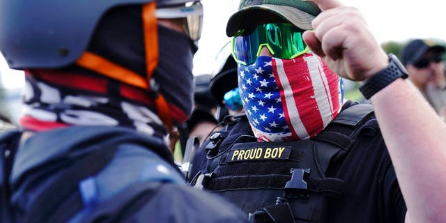 FILE - In this Sept. 26, 2020 file photo, a right-wing demonstrator gestures toward a counter protester as members of the Proud Boys and other right-wing demonstrators rally in Portland, Ore. (AP Photo/John Locher, File)