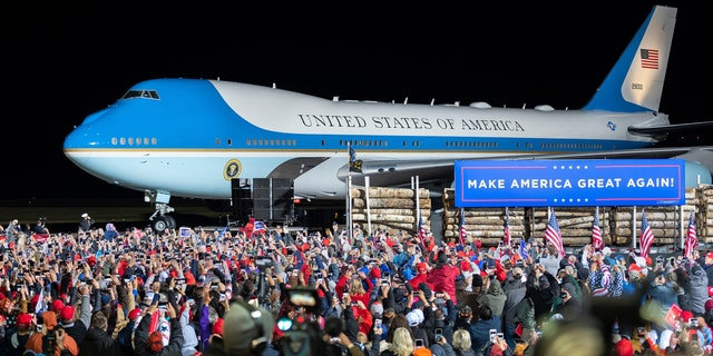 The crowd cheers as Air Force One arrives with President Trump at Duluth International Airport, Sept. 30, 2020, for Trump's campaign appearance in Duluth, Minn. (AP Photo/Jack Rendulich)