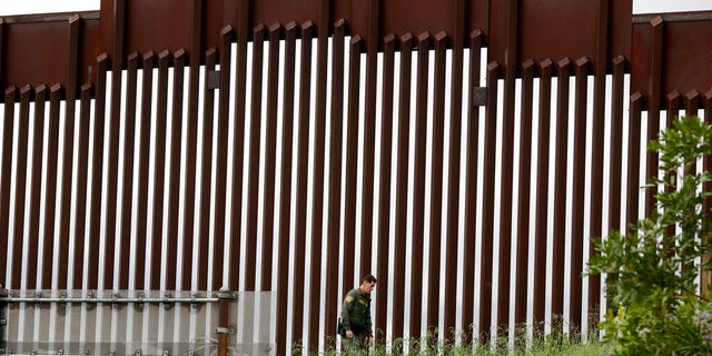 In this March 18 photo, a border patrol agent walks a border wall separating Tijuana, Mexico from San Diego, San Diego.  (AP Photo / Gregory Bull, File)