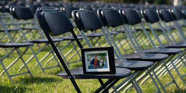 A photograph of Leo Villanueva who lost his life due the COVID-19, sits in one of the thousands of empty chairs, who represent a fraction of the more than 200,000 lives lost due the COVID-19 are seen during the National COVID-19 Remembrance, at The Ellipse outside of the White House, Sunday, Oct. 4, 2020, in Washington. (AP Photo/Jose Luis Magana)
