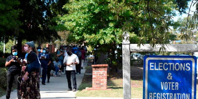 Voters wait in line outside the Richland County election office on the first day of in-person absentee voting in South Carolina on Monday, Oct. 5, 2020, in Columbia, S.C. A number of counties have polling places where people can vote almost like they would in person on Election Day, instead of having to mail in their absentee ballot. (AP Photo/Meg Kinnard)