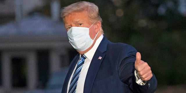 President Donald Trump gives a thumbs-up as he returns to the White House Monday, Oct. 5, 2020, in Washington, after leaving Walter Reed National Military Medical Center, in Bethesda, Md. (AP Photo/Alex Brandon)