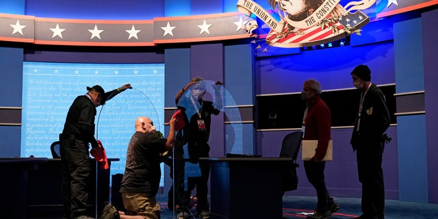 Workers clean protective plastic panels onstage between tables for Vice President Mike Pence and Democratic vice presidential candidate, Sen. Kamala Harris, D-Calif., as preparations take place for the vice presidential debate in Kingsbury Hall at the University of Utah, Tuesday, Oct. 6, 2020, in Salt Lake City. (AP Photo/Patrick Semansky)