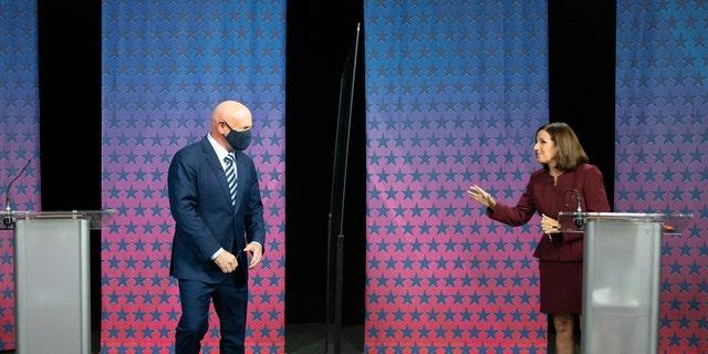 Democratic challenger Mark Kelly, left, arrives to debate U.S. Sen. Martha McSally, R-Ariz., right, at the Walter Cronkite School of Journalism in Phoenix, Ariz., Tuesday, Oct. 6, 2020. (Rob Schumacher/The Arizona Republic via AP, Pool)