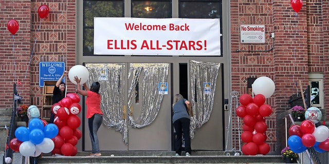 School staff help to decorate the front entrance of the Ellis Elementary School in Boston's Roxbury neighborhood before opening for the first day back of in person learning during the COVID-19 coronavirus pandemic, Thursday, Oct. 1, 2020. (David L Ryan/The Boston Globe via AP)