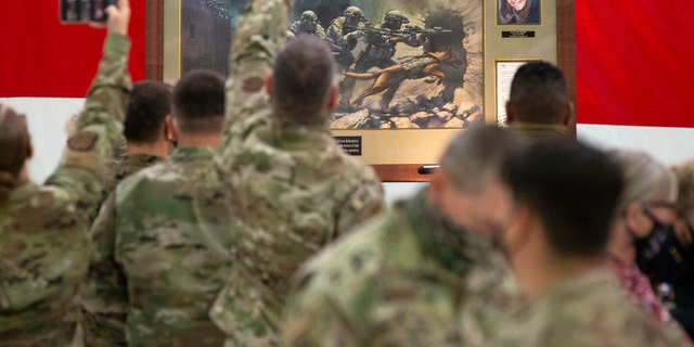 Members of the Air National Guard view the painting honoring Kayla Mueller, a humanitarian and Prescott native, during a ceremony at the Goldwater Air National Guard Base, Oct. 8, in Phoenix. (Rob Schumacher/The Arizona Republic via AP)