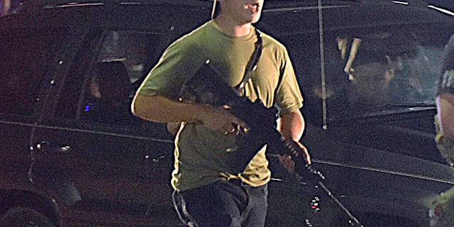 In this Tuesday, Ago. 25, 2020, file di foto, Kyle Rittenhouse carries a weapon as he walks along Sheridan Road in Kenosha, Wis., during a night of unrest following the weekend police shooting of Jacob Blake. In a document filed Thursday, Ott. 8, 2020, defense attorneys say sending Rittenhouse, who is accused of killing two protesters days after Jacob Blake was shot by police in Kenosha, Wis., to stand trial in Wisconsin would 'turn him over to the mob.' (Adam Rogan/The Journal Times via AP, File)