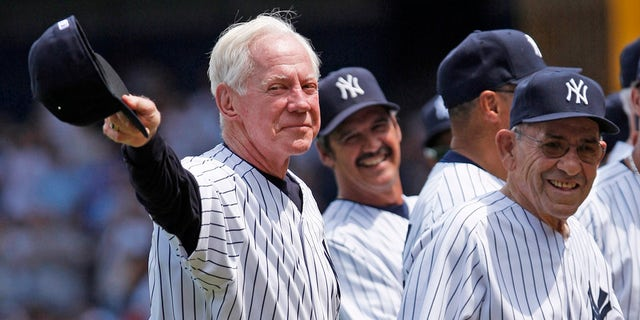 In this July 7, 2007 file photo, former New York Yankees pitcher Whitey Ford, left, acknowledges the crowd during introductions as Yogi Berra, right looks on before the Old Timer's game at Yankee Stadium in New York. A family member tells The Associated Press on Friday, Oct. 9, 2020, that Ford died at his Long Island home Thursday night. (AP Photo/Julie Jacobson, File)