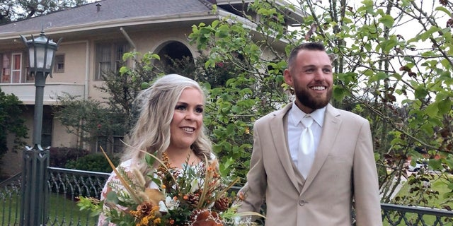 In this image made from video, Ian and Taylor Gaspard from Abbeville speak to a reporter after getting married Thursday. Hurricane Delta sped up the Louisiana couple's wedding by a few days but judging by the smiles on the bride and groom it certainly didn't dampen the affair. (AP Photo/Rebecca Santana)