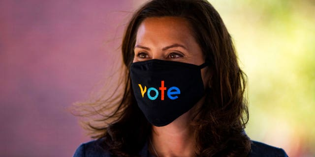"""Michigan Gov. Gretchen Whitmer wears a mask with the word """"vote"""" displayed on the front during a roundtable discussion on healthcare, Wednesday Oct. 7, 2020, in Kalamazoo, Mich. (Nicole Hester/Ann Arbor News via AP)/"""