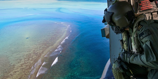 In this Sept. 25, 2020, photo provided by the Royal Australian Navy, Leading Seaman Daniel Atkins looks out over Elizabeth Reef in search of unexploded ordnance on an MRH-90 helicopter from HMAS Adelaide. The 45-kilogram (100-pound) bomb was found by a fisherman on Elizabeth Reef near Lord Howe Island, about 550 kilometers (340 miles) off New South Wales state. (Sgt. Jake Sims/Royal Australian Navy via AP)