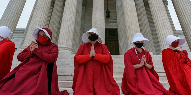 "Activists opposed to the confirmation of President Donald Trump's Supreme Court nominee, Judge Amy Coney Barrett, are dressed as characters from ""The Handmaid's Tale,"" at the Supreme Court on Capitol Hill in Washington, Sunday, Oct. 11, 2020. (AP Photo/J. Scott Applewhite)"