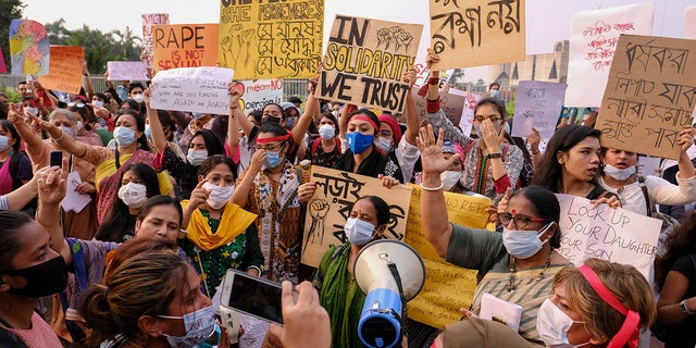 Women's rights activists and others protesting against gender-based violence hold placards outside the Parliament in Dhaka, Bangladesh, Friday, Oct.9, 2020. Bangladesh's Cabinet has approved an increase in the maximum punishment in rape cases to death from life imprisonment after a series of recent sexual assaults triggered protests. (AP Photo/ Mahmud Hossain Opu)