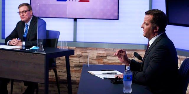 Republican challenger Daniel Gade, right, gestures during a debate with U.S. Sen. Mark Warner, left, at a television studio Tuesday, Oct. 13, 2020, in Richmond, Va. (AP Photo/Steve Helber)