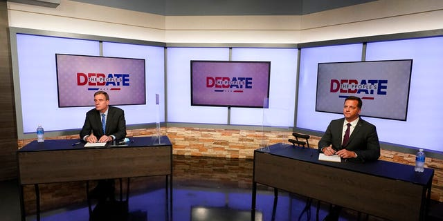 U.S. Sen. Mark Warner, D-Va., left, and Republican challenger Daniel Gade, right, prepare for a debate at a television studio Oct. 13, in Richmond, Va. (AP Photo/Steve Helber)