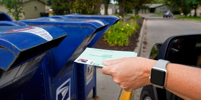A person dumps applications for mail in the mailbox in Omas, Heaven.  (AP Photo / Nati Harnik, File)