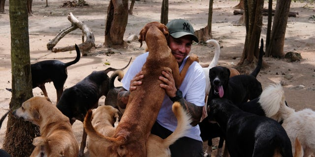 Ricardo Pimentel is greeted by dogs that he rescued at his Tierra de Animales shelter in Leona Vicario, Mexico, on Oct. 13.