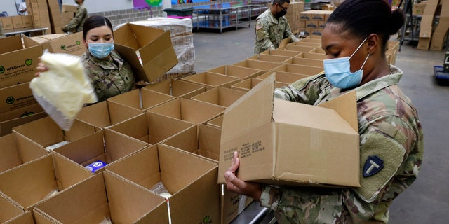 Texas National Guard soldiers Spc. Esmeralda Zuniga, 剩下, and Spc. Samantha McClasky, 对, load boxes with various dairy products at the Houston Food Bank on Oct. 14. (AP Photo/Michael Wyke)
