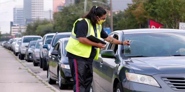 Volunteer Sharely Gomez marks the windshield after taking information from clients in their cars as they wait in line at West Houston Assistance Ministries. (AP Photo/Michael Wyke)