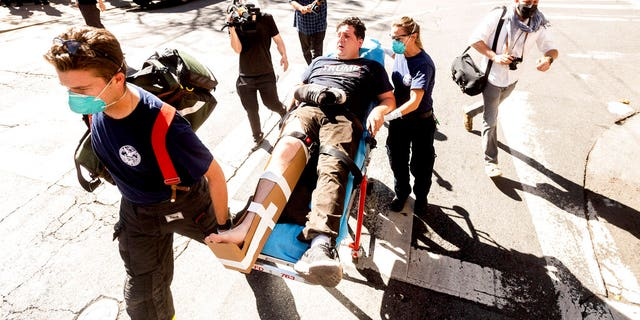 Doctors are transporting a supporter of President Donald Trump to an ambulance after he was attacked by counter-protesters in San Francisco on Saturday, October 17, 2020. About a dozen pro-Trump protesters were greeted by several hundred counter-protesters as they tried to rally.  (AP Photo / Noah Berger)