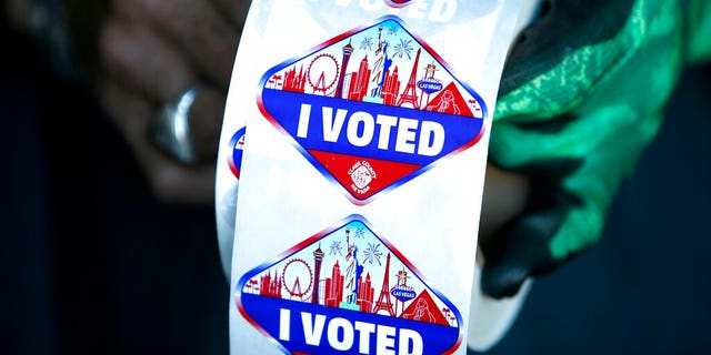 "FILE: A poll worker displays ""I Voted"" stickers during the first day of early voting in Las Vegas."