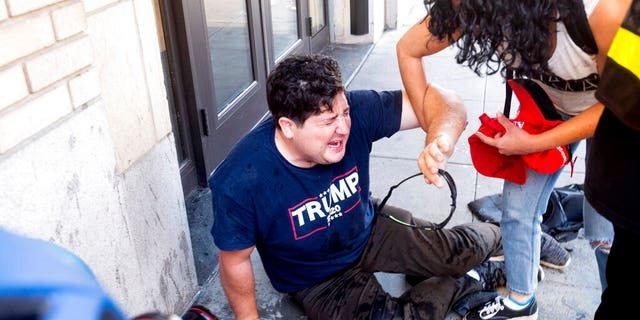 A supporter of President Donald Trump is on the ground after he was attacked by counter-protesters in San Francisco, on Saturday, October 17, 2020. About a dozen pro-Trump protesters were greeted by hundreds of counter-protesters as they tried to rally.  (AP Photo / Noah Berger)