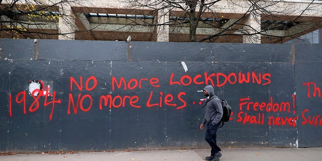 A man walks past anti-lockdown graffiti in Manchester, England, Monday, Oct. 19, 2020 as the row over Greater Manchester region's coronavirus status continues. Britain's government says discussions about implementing stricter restrictions in Greater Manchester must be completed Monday because the public health threat caused by rising COVID-19 infections is serious and getting worse. (Peter Byrne/PA via AP)