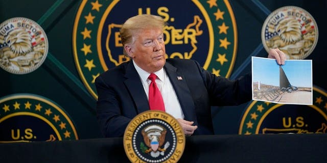 FILE - In this June 23, 2020 file photo, President Trump holds an image of the U.S. border wall being built between the U.S. and Mexico as he participates in a border security briefing at United States Border Patrol Yuma Station in Yuma, Ariz. (AP Photo/Evan Vucci)