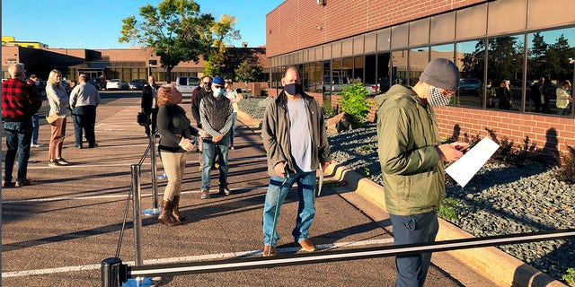 Voters line up outside of the Minneapolis early voting center as Minnesota opened early voting for the general election. (AP Photo/Steve Karnowski, File)