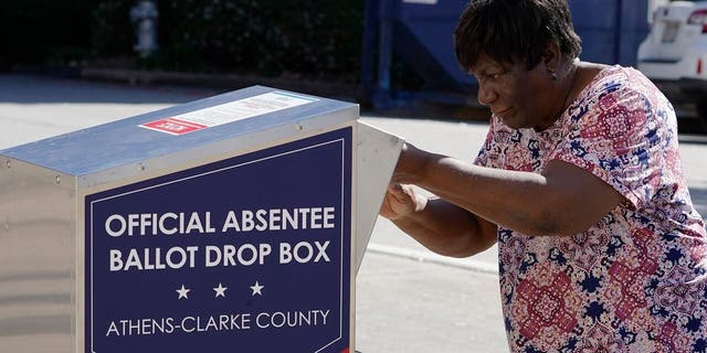 A voter drops their ballot off during early voting, Monday, Oct. 19, 2020, in Athens, Ga. (AP Photo/John Bazemore)