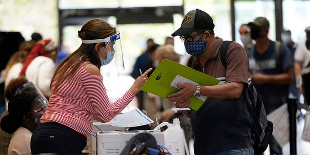 An election worker, left, gives instructions for voting at an early voting site, Monday, Oct. 19, 2020, in Miami. (AP Photo/Lynne Sladky)