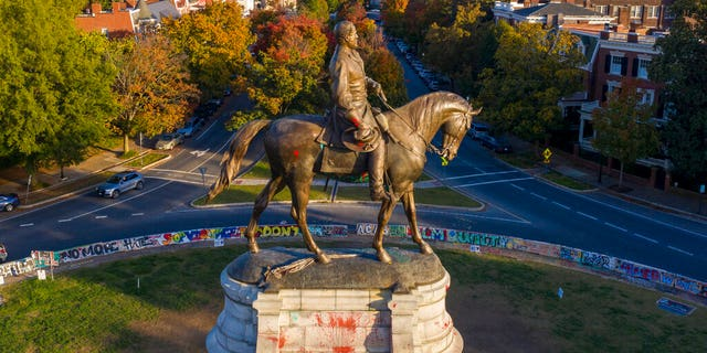 The afternoon sun illuminates the statue of Confederate General Robert E. Lee on Monument Ave in Richmond, Va., Okt.. 19. (AP Photo/Steve Helber)