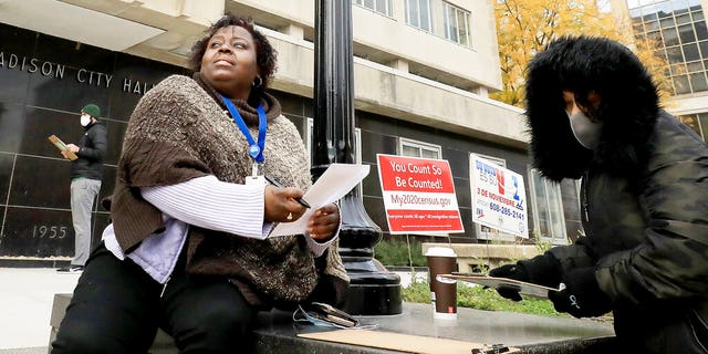 Madison, Wis. residents Theola Carter, left, and Carrie Braxton fill out their ballots on the first day of the state's in-person absentee voting window for the Nov. 3 election.