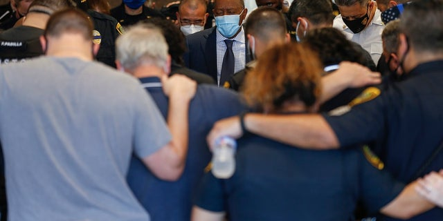 Mayor Sylvester Turner, center, prays with Houston Police officers, after learning Sgt. Harold Preston died at Memorial Hermann Hospital on Oct. 20, in Houston. Two officers were shot by a suspect during a domestic violence call at an apartment complex. (Godofredo A. Vásquez/Houston Chronicle via AP)