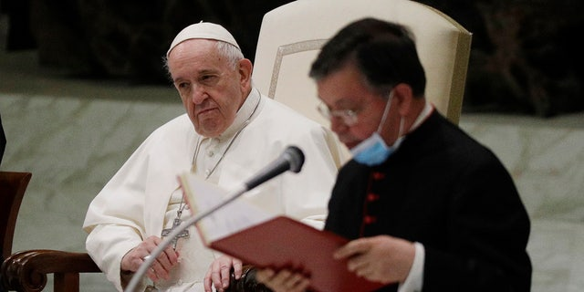 Pope Francis listens to a priest introducing the group of faithful attending the weekly general audience in the Paul VI hall at the Vatican, Wednesday, Oct. 21, 2020. (AP Photo/Gregorio Borgia)