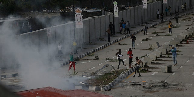 Protesters run away as police officers use teargas to disperse people demonstrating against police brutality in Lagos, Nigeria, Wednesday Oct. 21, 2020. After 13 days of protests against alleged police brutality, authorities have imposed a 24-hour curfew in Lagos, Nigeria's largest city, as moves are made to stop growing violence. ( AP Photo/Sunday Alamba)