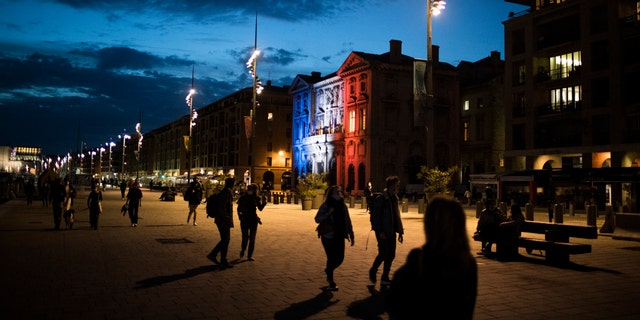 Pedestrians walk along Marseille's Old Port as the town hall is lit up in the French Tricolor to honor slain teacher Samuel Paty, Wednesday, Oct. 21, 2020. French history teacher Samuel Paty was beheaded in Conflans-Sainte-Honorine, northwest of Paris, by an 18-year-old Moscow-born Chechen refugee, who was later shot dead by police. (AP Photo/Daniel Cole)