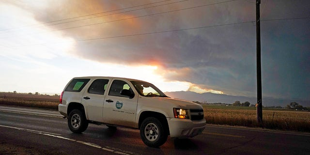 Smoke rises from mountain ridges as several wildfires burn in the state Wednesday, Oct. 21, 2020, as traffic moves along 75th street in Niwot, Colo. (Associated Press)