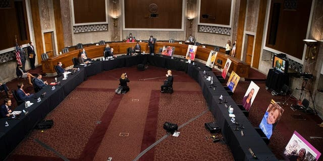 Images of people who've been helped by the Affordable Care Act (ACA) occupy the seats of Democratic senators boycotting a Senate Judiciary Committee business meeting on the nomination of Judge Amy Coney Barrett to be an associate justice of the U.S. Supreme Court, Thursday, Oct. 22, 2020 on Capitol Hill in Washington. (Caroline Brehman/Pool via AP)