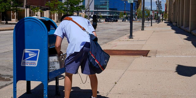 Aug. 18, 2020: A postal worker empties a box near the Fiserv Forum in Milwaukee. Parts of the politically coveted battleground states of Wisconsin, Michigan, Pennsylvania and Ohio fell short of delivery goals by wide margins as the agency struggles to regain its footing after a tumultuous summer. (AP Photo/Morry Gash)