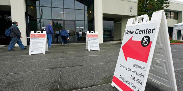 People walk near a sign at the King County election headquarters Oct. 23, 2020.