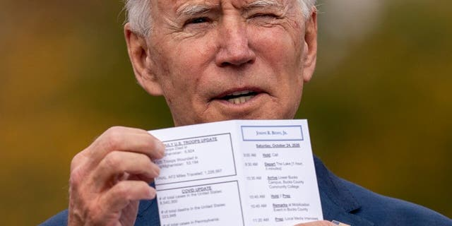 Democratic presidential candidate former Vice President Joe Biden holds up his daily schedule which has a daily update on US Troop deaths and wounded numbers as he speaks at a drive-in campaign stop at Bucks County Community College in Bristol, Pa., Saturday, Oct. 24, 2020. (AP Photo/Andrew Harnik)