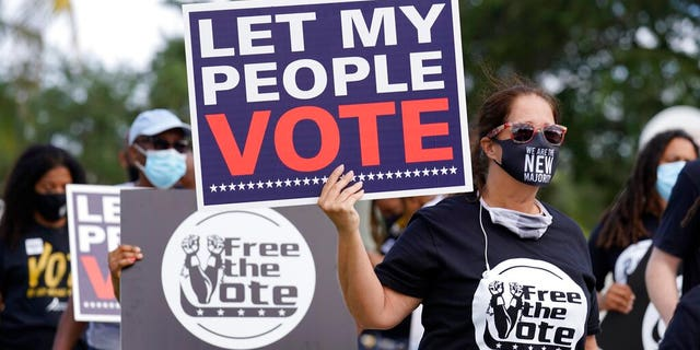 Supporters of restoring Florida felons' voting rights march to an early voting precinct, Saturday, Oct. 24, 2020, in Fort Lauderdale, Fla.